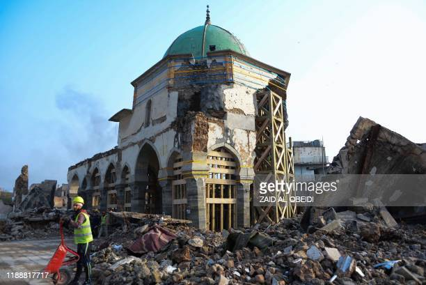 An Iraqi worker clears rubble during the reconstruction of the Great Mosque of AlNuri in Mosuls warravaged old town on December 15 2019 In December...