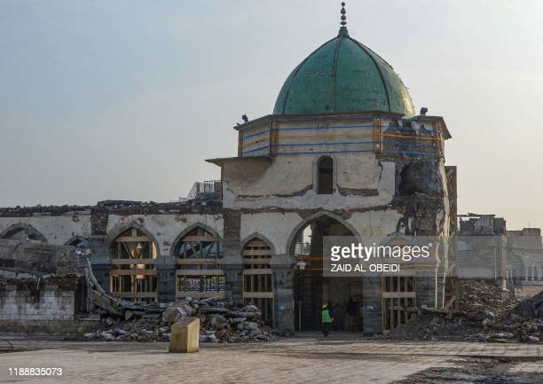 An Iraqi worker enters the Great Mosque of Al-Nuri during the complex's reconstruction in Mosuls war-ravaged old town, on December 15, 2019. - In...