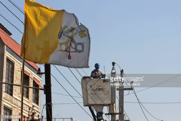 An Iraqi worker fixes electric cables as the flag of the Vatican flies in front of the Saint Joseph Chaldean Catholic church, ahead of the visit of...