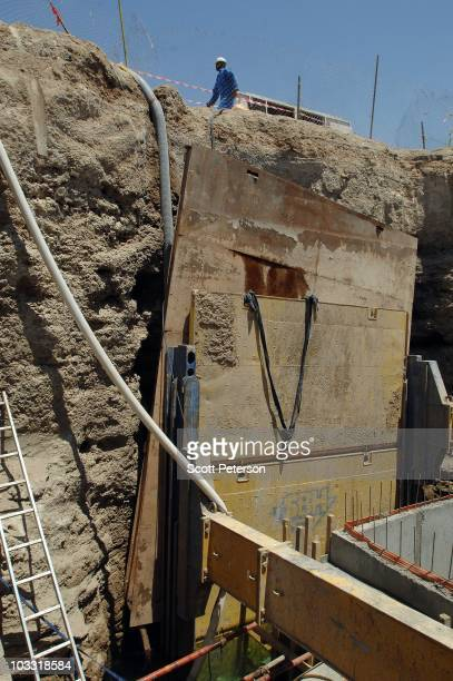 An Iraqi worker passes by as officers of the US Army Corps of Engineers inspect USfunded trunk line excavations in Fallujah Iraq on July 23 2010 The...
