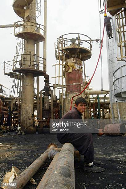 An Iraqi worker sits while repairing the Kissik oil refinary October 29 2003 in Ninewa Province Iraq The refinary is running at 60 percent of...