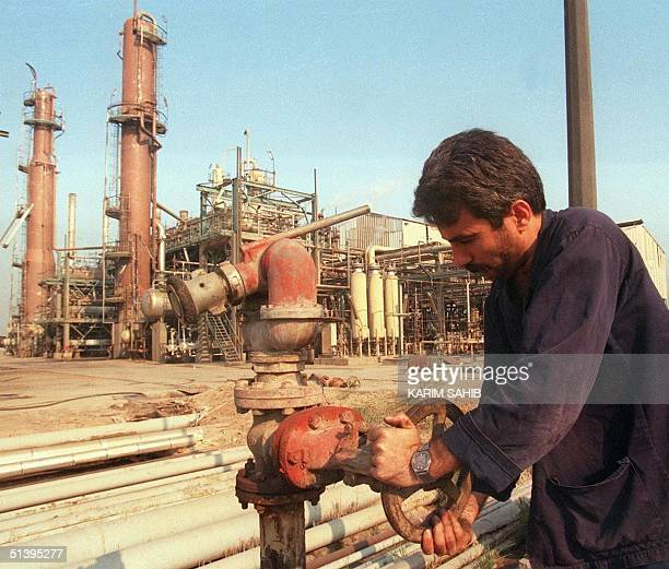 An Iraqi worker tends to pipes at an oil refinery in the southern Iraqi port of Basra 08 June 1999. Iraqi accusations that Kuwait has been stealing...