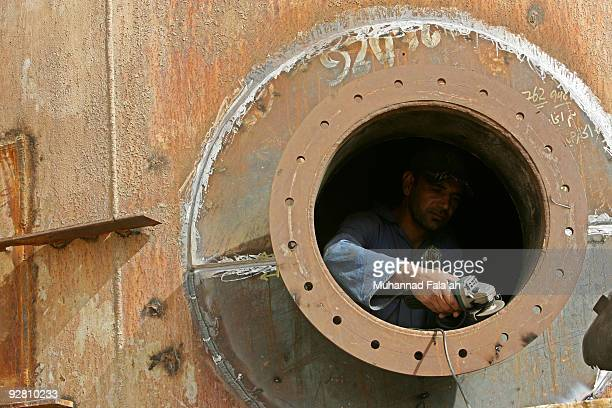 An Iraqi worker uses tools on an oil tank at the Daura oil refinery on November 5 2009 in Baghdad Iraq Iraq and a grouping of US and European oil...