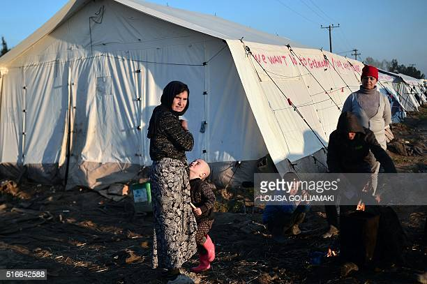 An Iraqi Yazidi family warms around a bonfire at the makeshift camp at the GreekMacedonian border near the village of Idomeni early on March 20 2016...