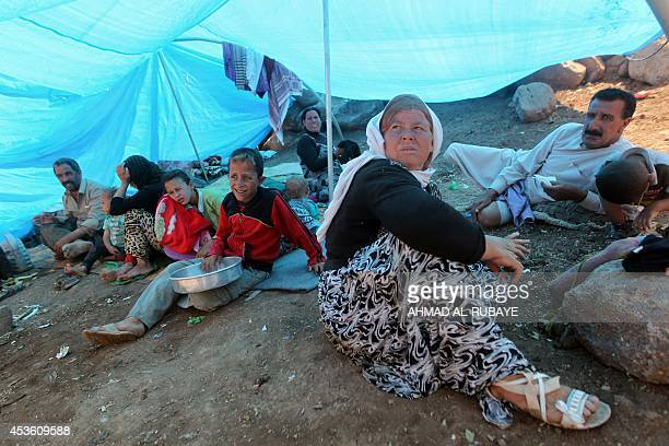 An Iraqi Yazidi refugee family gathers under a tent at Newroz camp in Hasaka province north eastern Syria on August 14 after fleeing Islamic State...