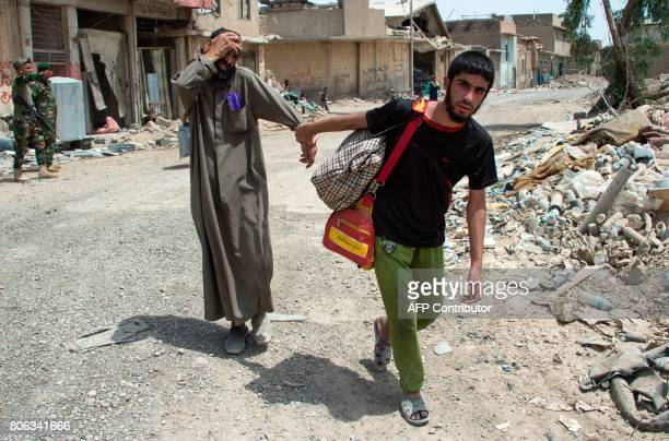 An Iraqi young man pulls another by the nad as they flee the Old City of Mosul on July 3 during the government forces' ongoing offensive to retake...