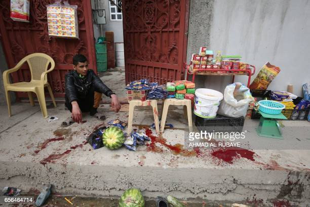 TOPSHOT An Iraqi young man sits in shock next to a blood pool after a mortar shell was fired by Islamic State group jihadists on civilians in...