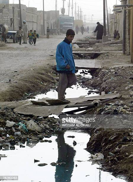 An Iraqi youth crosses an uncovered sewage canal at the area of Fdailiyah southeast of Baghdad 06 December 2007 Many of Baghdad's neighborhoods lack...