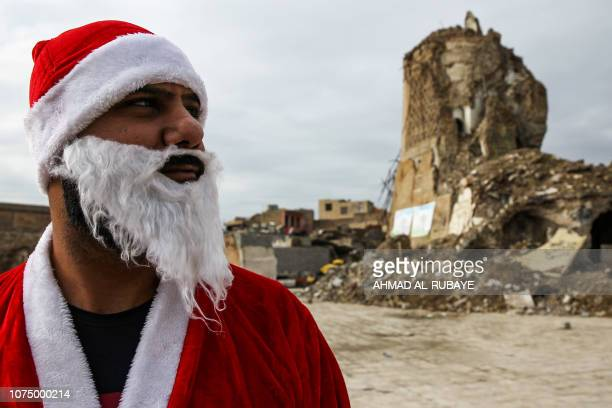 An Iraqi youth dressed in a Father Christmas suit stands near the remains of 'AlHadba' leaning minaret in the ruins of the Great Mosque of AlNuri as...