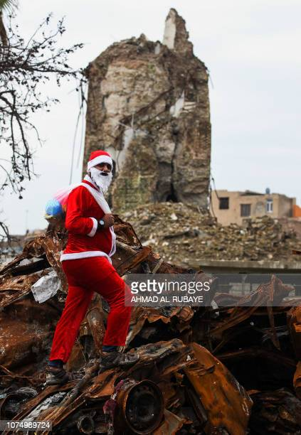 An Iraqi youth dressed in a Father Christmas suit stands on car wrecks near the remains of AlHadba leaning minaret in the ruins of the Great Mosque...