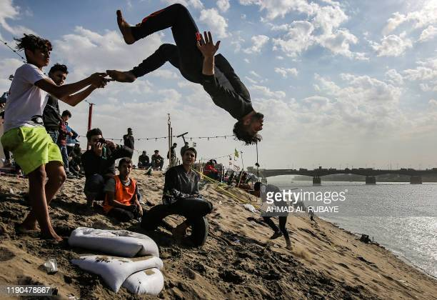 An Iraqi youth performs a backflip along the bank of the Tigris river near antigovernment protest tents by the Senak bridge on December 25 2019