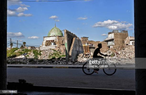 An Iraqi youth rides a bicycle past the Nuri mosque in the old town of the northern city of Mosul, a site heavily damaged by Islamic State group...