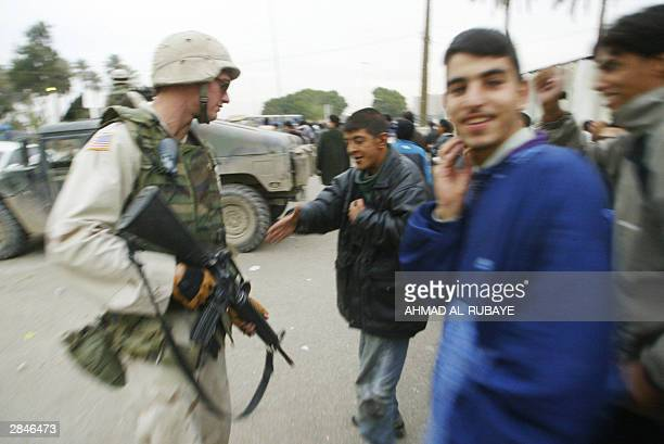 An Iraqi youth tries to shake hands with a US soldier standing guard outside Baghdad's alZawra stadium after the final between rival Baghdad clubs...