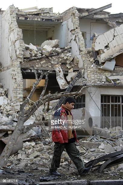 An Iraqi youth walks past destroyed houses a day after a bomb blast near the Hamra Hotel in Jadriyah south of Baghdad on January 26 2010 Three huge...