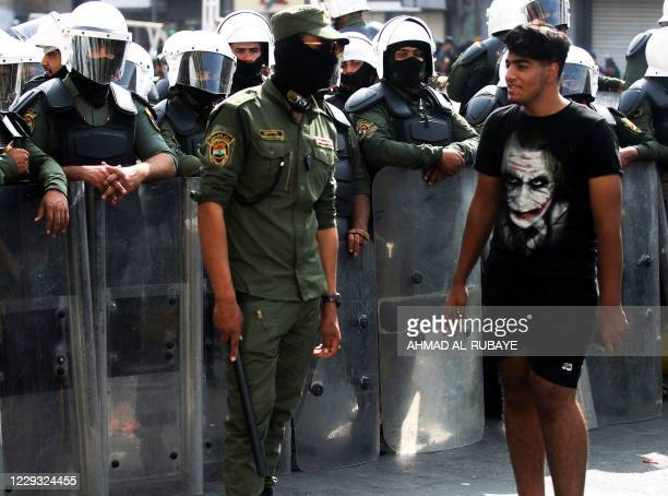 An Iraqi youth walks past riot police in the capital Baghdad's Tahrir Square on October 28 during a cleanup operation by the security forces,...