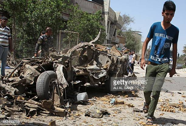 An Iraqi youth walks past the remains of a vehicle at the site of an explosion in Baghdad on April 9 2014 Six car bombs rocked mainly Shiitepopulated...