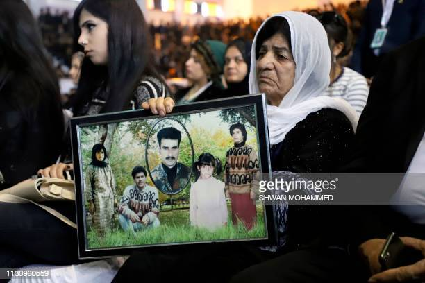 An Iraqi-Kurd carries portraits of relatives during a gathering in Halabja on March 16 at the monument for victims of the gas massacre that killed...