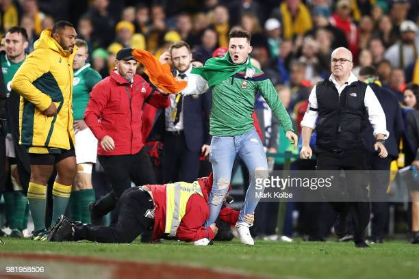 An Ireland supporter who invaded the pitch to celebrate victory with the Ireland team is tackled by security after the Third International Test match...