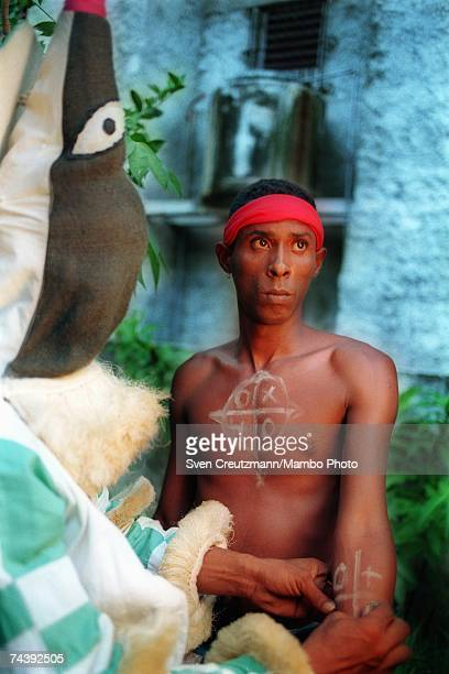 An 'Ireme' or 'Diablito' paints a new 'Indeceme' with secret symbols before an Abacua initiation ceremony for new members on July 16 2000 in the...