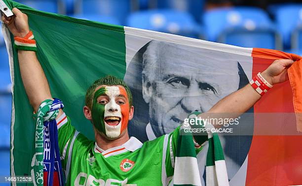 An Irish fan poses with his national flag with a portrait of Ireland's Italian coach Giovanni Trapattoni before the Euro 2012 football championships...