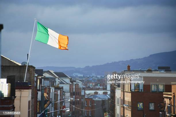 an irish flag fliying over the skyline of dublin city, ireland - david soanes stock pictures, royalty-free photos & images