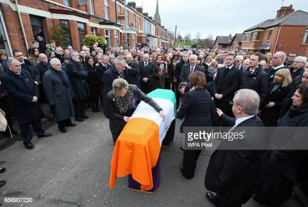 An Irish flag is placed upon the coffin ahead of the funeral of former Northern Ireland Deputy First Minister Martin McGuinness outside his home in...