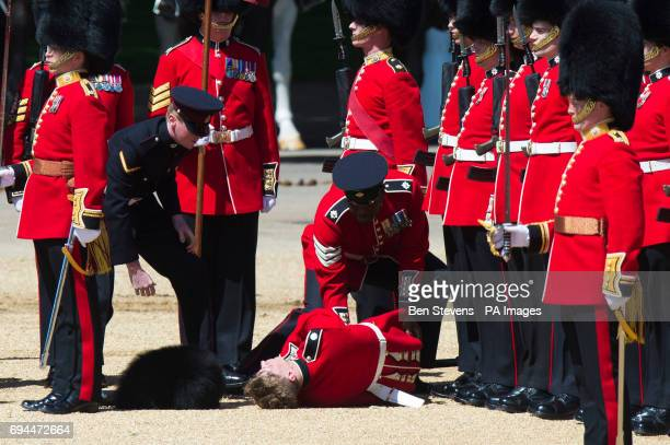 An Irish Guard collapses before being taken away on a stretcher during the Colonel's Review the final rehearsal of the Trooping the Colour the...