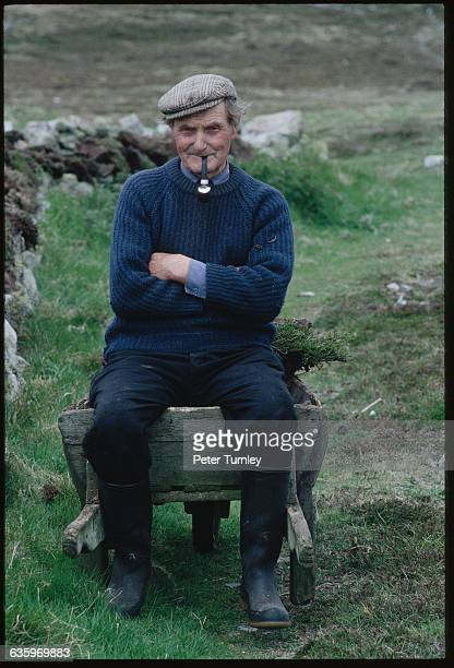 An Irish man smokes a pipe while sitting on a wooden wheelbarrow in a rural area of Tory Island Ireland
