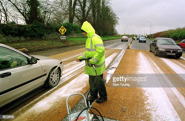An Irish Ministry of Agriculture employee sprays a car's tires with disinfectant April 17 2001 at a Garda foot and mouth disease checkpoint in County...