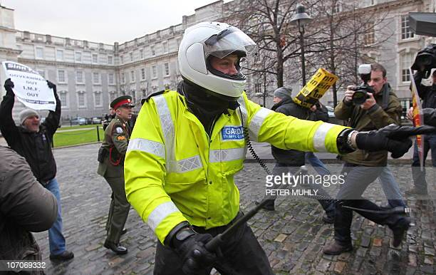 An Irish policeman attempts to hold back protestors as they break through the front gates of the Irish Prime Ministers office in Dublin Ireland on...