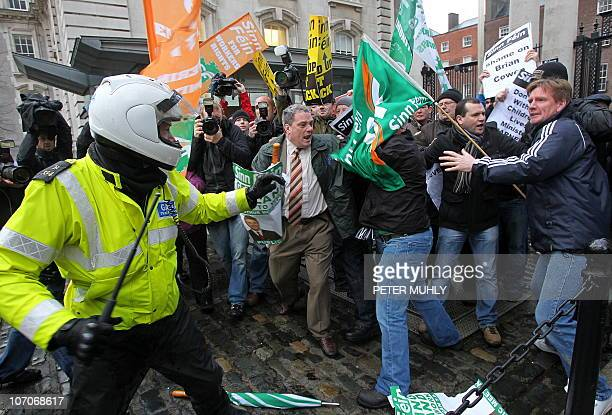 An Irish policeman is confronted by protestors as they break through the front gates of the Irish Prime Ministers office in Dublin Ireland on...