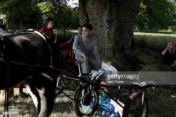 An Irish Traveller sits in the shade and watches young men racing horses at the Appleby Horse Fair on June 4 2016 in Appleby England The annual horse...