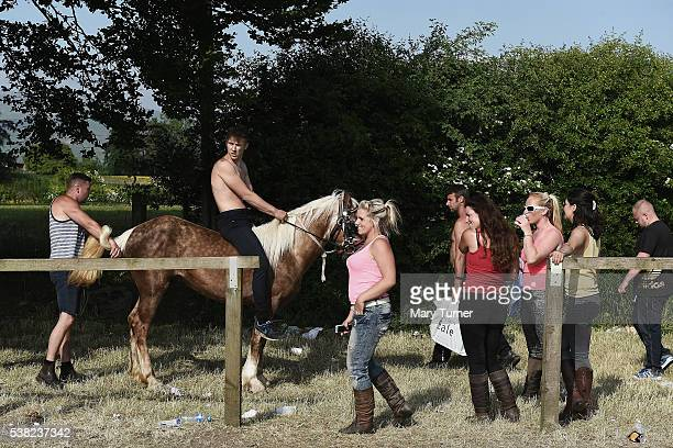 An Irish traveller sits on a horse in the shade and watches young men racing horses at the Appleby Horse Fair on June 4 2016 in Appleby England The...