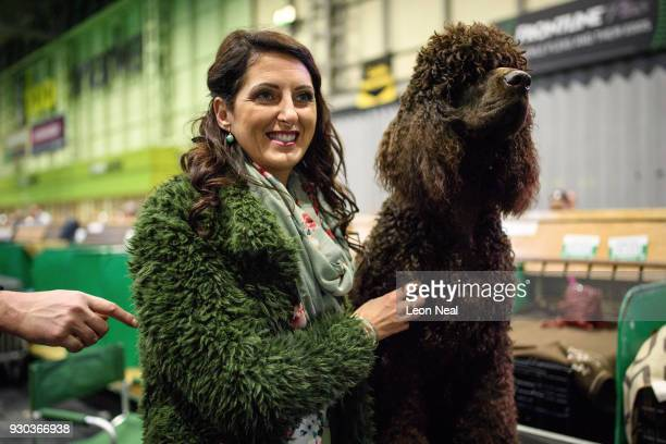 An Irish Water Spaniel named Kandrelli Jack Snipe is hugged by a woman on day four of the Cruft's dog show at the NEC Arena on March 11 2018 in...