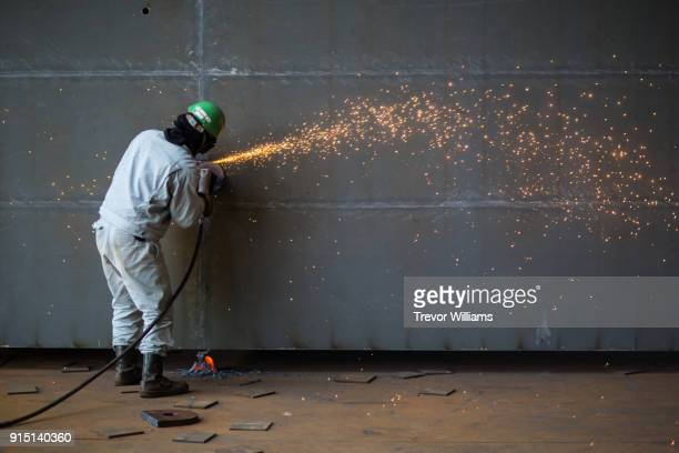 an iron worker grinding large ship parts with sparks flying - dureza - fotografias e filmes do acervo