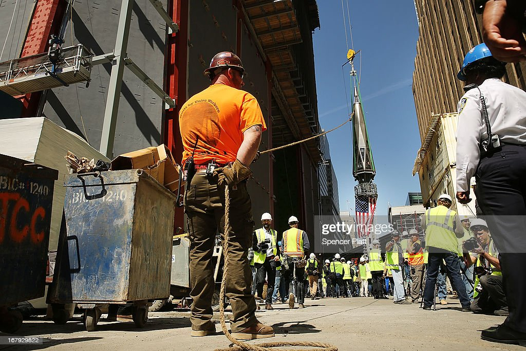 An iron worker holds a rope as the last 75-foot section of the 408-foot spire is hoisted onto a temporary platform on the top of One World Trade Center on May 2, 2013 in New York City. When bolted into place at a later date, the spire will make One World Trade Center the tallest building in the Western Hemisphere.The raising of the spire, which comes on the second anniversary of the death of Osama bin Laden, will make One World Trade Center 1,776 feet tall. One World Trade Center is built on the site where the September 11, 2001 attacks toppled the original World Trade Center towers.