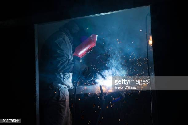 an iron worker welding in a shipbuilding factory - dureza - fotografias e filmes do acervo