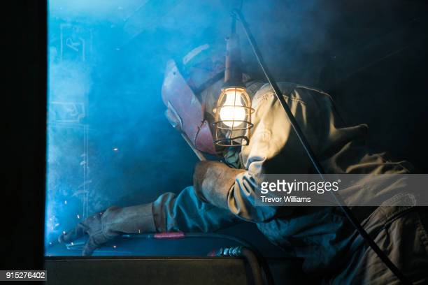 An iron worker welding in a shipbuilding factory