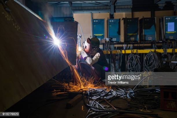 an iron worker welding in a shipbuilding factory - shipyard stock pictures, royalty-free photos & images