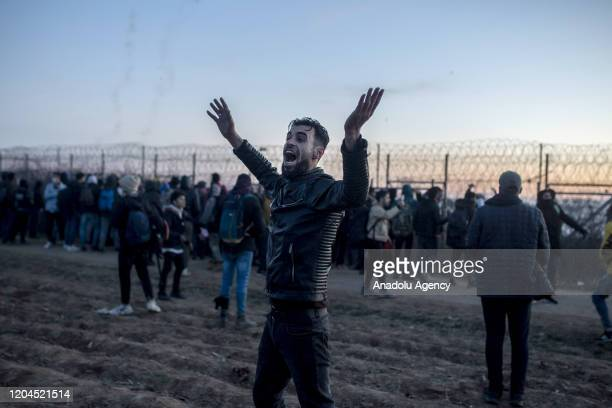 An irregular migrant reacts to the intervention of Greek border guards with tear gas and stun grenades to disperse irregular migrants at the land...