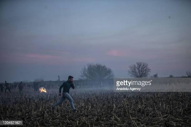 An irregular migrant runs away amid tear gas smokes launched by Greek border guards at the land border between Greece and Turkey, Karaagac...