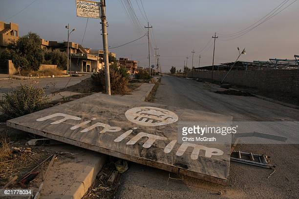 An ISIL billboard is seen destroyed in the middle of the road on November 8 2016 in Qaraqosh Iraq The NPU is a military organization made up of...