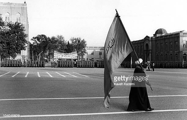 An Islamic cleric marches with a flag during a parade at a military academy in Tehran, Iran, during the Iran-Iraq War, 14th October 1981.