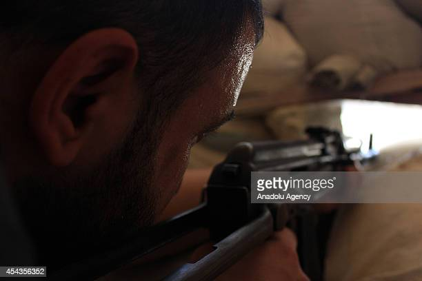 An Islamic Front member aims at the Syrian regime's snipers deployed in the municipality building damaged during the clashes in Aleppo Syria on...
