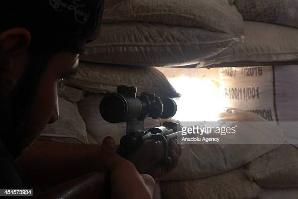 An Islamic Front member aims at the Syrian regime's snipers deployed in headquarters of regime forces in Aleppo Syria on 1 September 2014