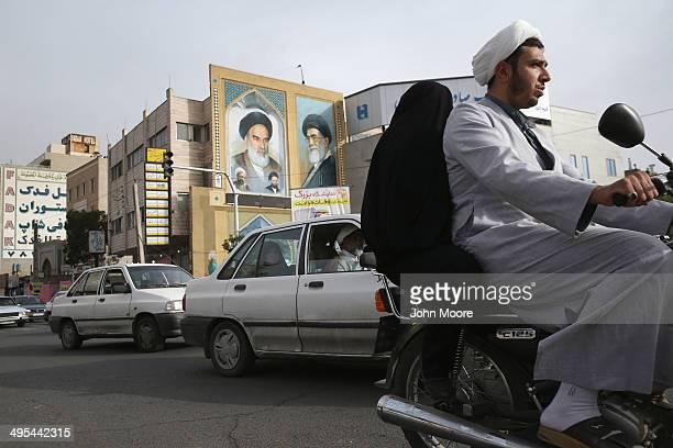 An Islamic Mullah and his wife ride past portraits of the late Ayatollah Khomeini , and Iran's current supreme leader Ayatollah Khamenei on June 3,...