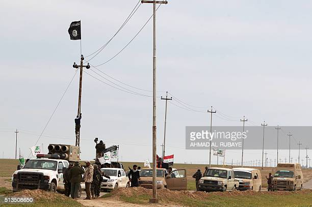 An Islamic State group flag flutters above Iraqi Shiite fighters from the Popular Mobilisation units on March 3 during an operation in the desert of...