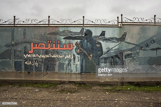 An Islamic State propaganda mural painted on a wall in east Mosul Iraq on January 28 2017 The painting featuring an armed Islamic State fighter with...