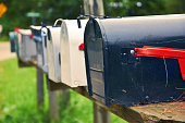 An isolated row of metal US mail boxes on wooden post in the countryside. Spider webs in one of them. Mail concept. New York City. United States