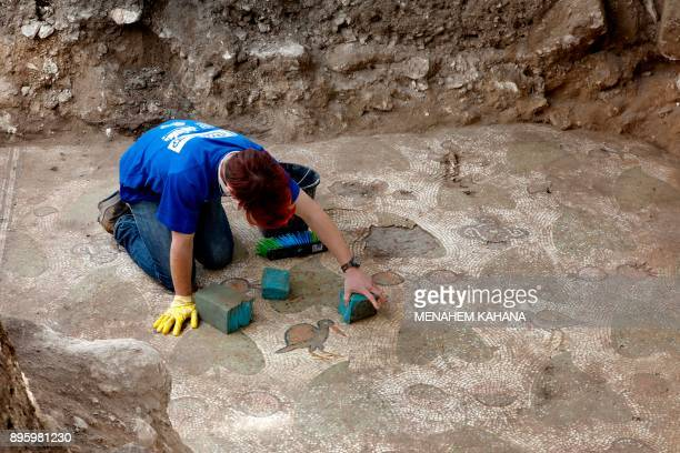 An Israel Antiquities Authority volunteer uncovers a mosaic floor part of the remains of a 1500yearold monastery and church recently discovered in...